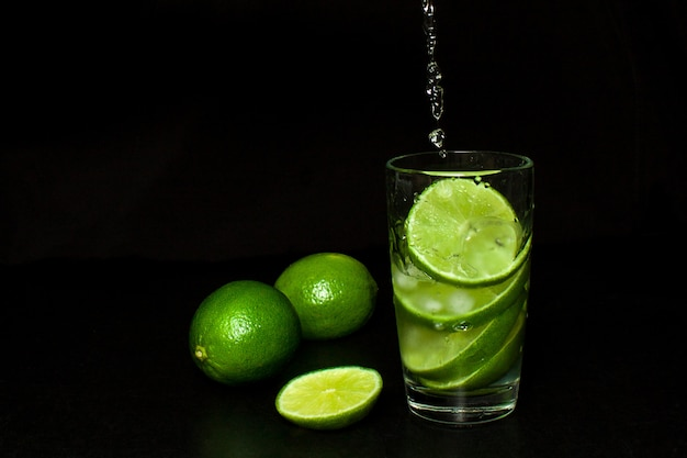 Strumień wlewa się do szklanki zimnego napoju z lodem i świeżymi dojrzałymi zielonymi limonkami na czarno Premium Zdjęcia