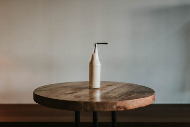 Strzał Szklana Butelka Z Czarną Słomką Wypełnioną Napojem Na Brązowym Drewnianym Stole Darmowe Zdjęcia