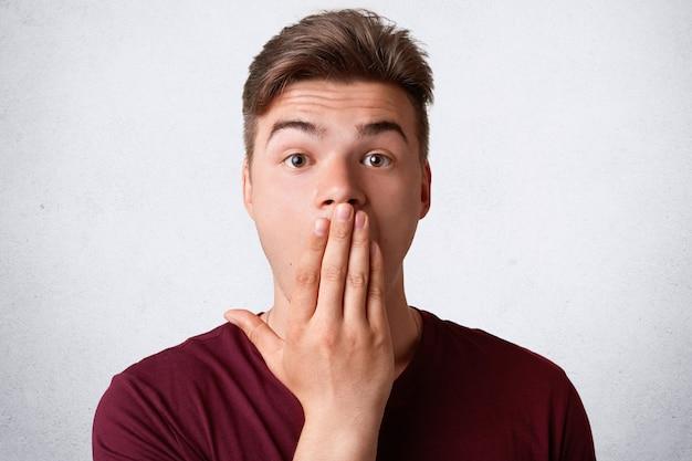 Strzał W Głowę Stresującego Zaskoczonego Mężczyzny Zakrywa Usta I Patrzy Na Zadziwiających Ludzi Darmowe Zdjęcia