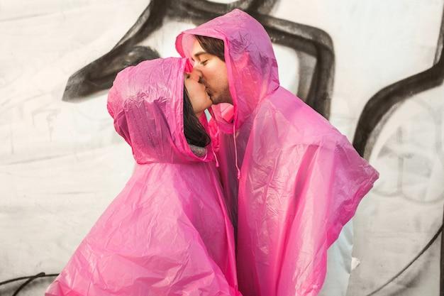 Strzał Zbliżenie Mężczyzny I Kobiety W Różowe Płaszcze Z Tworzywa Sztucznego Całujących Się Nawzajem Darmowe Zdjęcia
