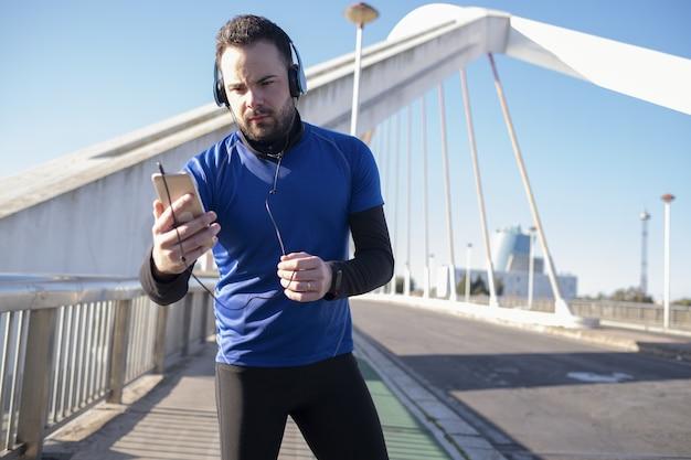 Strzał Zbliżenie Mężczyzny W Niebieskich Słuchawkach Za Pomocą Swojego Telefonu Komórkowego Podczas Joggingu Na Ulicy Darmowe Zdjęcia