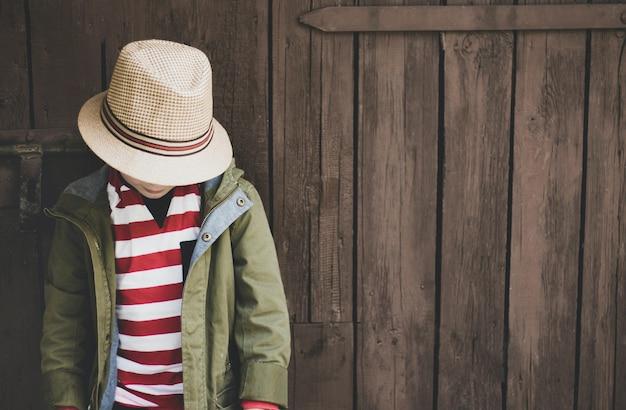 Strzał Zbliżenie Młodego Chłopca W Zielony Płaszcz, Koszula W Paski I Kapelusz Na Tle Drewnianych Darmowe Zdjęcia