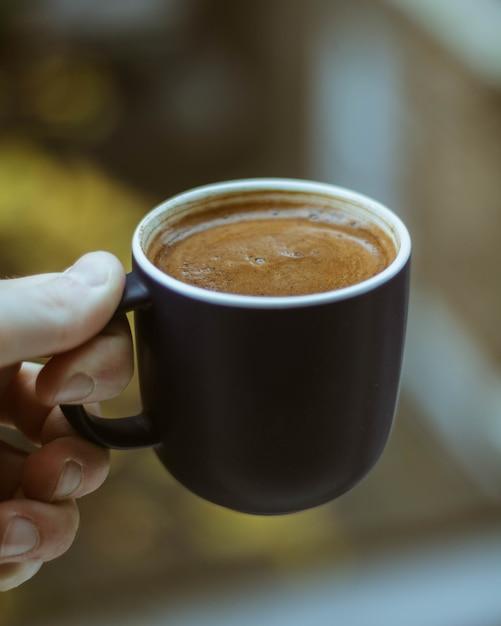 Strzał Zbliżenie Osoby Trzymającej Czarną Filiżankę Kawy Darmowe Zdjęcia