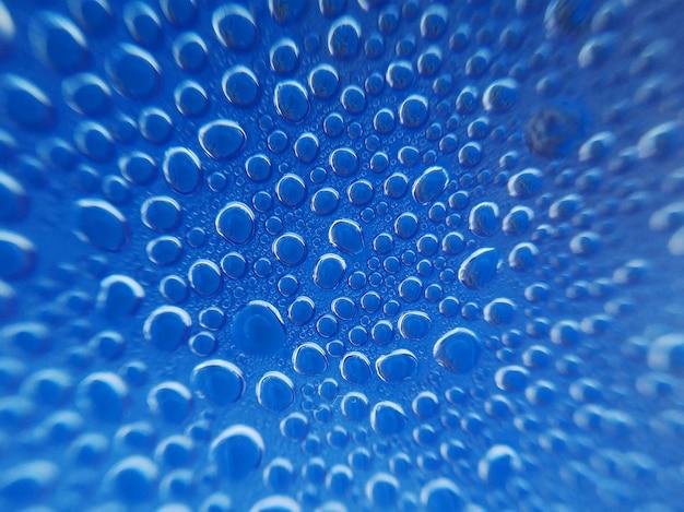 Strzał zbliżenie pary wody spada na niebieskim tle z promieniowych niewyraźne efekty Premium Zdjęcia