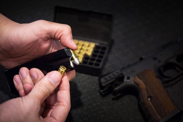 Strzelec przeładowuje magazynek pistoletowy, broń, pocisk z bloku pocisków na strzelnicy, aby strzelać Premium Zdjęcia
