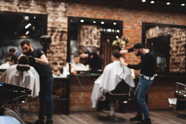 Strzyżenie głowy w zakładzie fryzjerskim, fryzjer ścina włosy na głowie klienta. Premium Zdjęcia