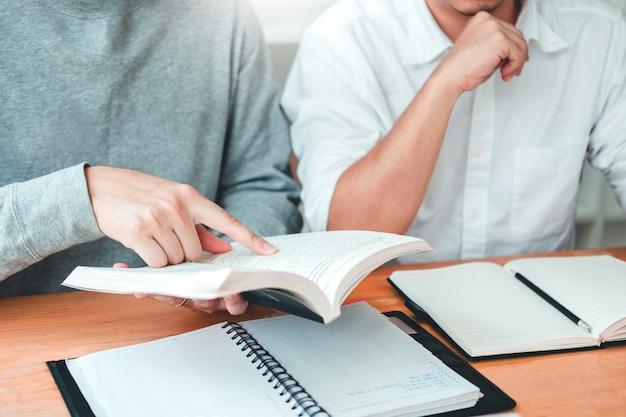 Studenci lub studenci studiujący i czytający razem w bibliotece. Premium Zdjęcia