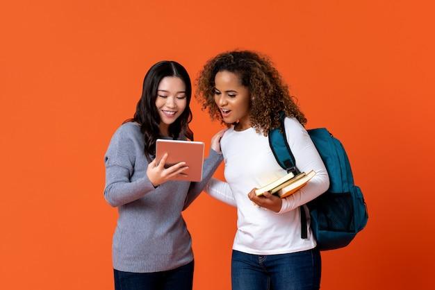 Studenci uniwersytetu jako przyjaciele patrzeje pastylka komputer Premium Zdjęcia