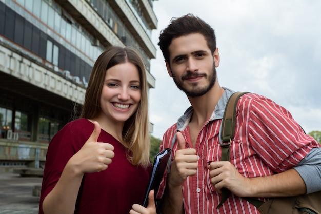 Studenci uniwersytetu pokazujący kciuki do góry Premium Zdjęcia