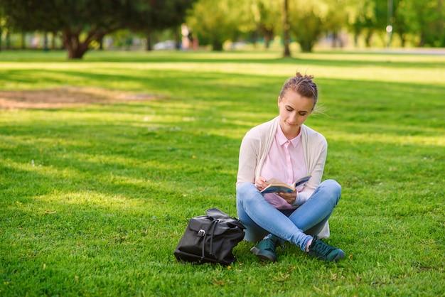 Studencka Kobieta Studiuje Outdoors W Kampusie Uniwersyteckim Przy Zmierzchem. Premium Zdjęcia