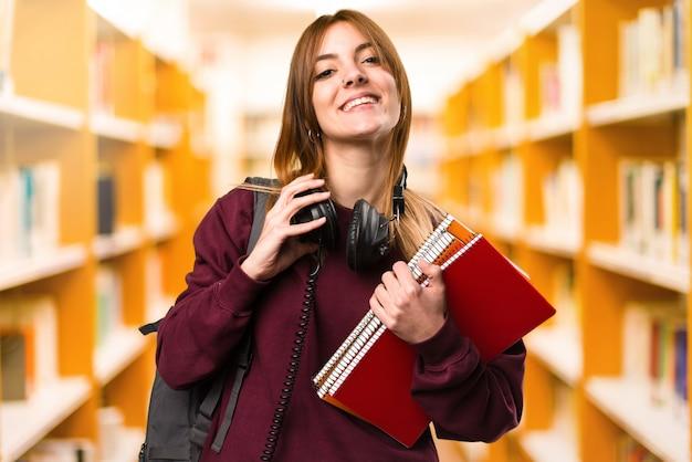 Studenckiej kobiety słuchająca muzyka na unfocused tle. powrót do szkoły Premium Zdjęcia