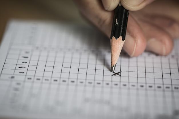 Student Zdaje Egzaminy, Egzamin Pisemny Na Papierowym Arkuszu Odpowiedzi Forma Optyczna Znormalizowanego Testu Na Biurku Premium Zdjęcia