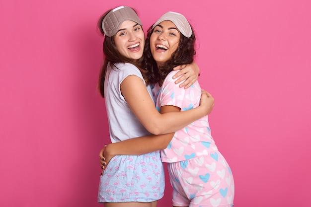 Studio Strzał Uśmiechniętych Uroczych Kobiet Z Maskami Do Spania, Ubranych W Piżamę, Stojących Targujących Się Na Tle Różanego Studia, Panie Targujące Się Nawzajem, Wyrażających Szczęście. Koncepcja Przyjaźni. Premium Zdjęcia