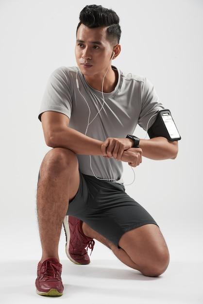 Studio strzelał azjatycki młody sportowiec klęczy i pozuje będący ubranym jego przyrząda Darmowe Zdjęcia
