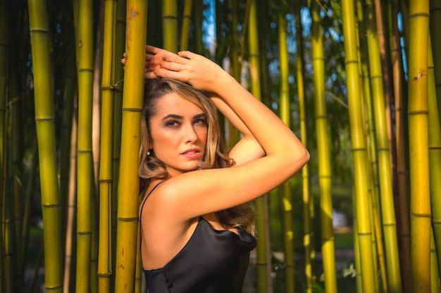 Styl życia Blondynka Kaukaska Dziewczyna W Czarnej Sukience Na Ramiączkach W Pięknym Bambusie W Parku Na Zewnątrz Dziewczyna Zrelaksowana I Ciesząca Się Spokojem Przebywania Na świeżym Powietrzu Premium Zdjęcia