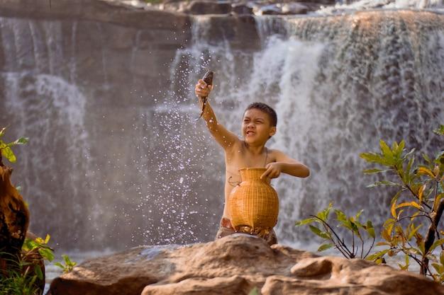 Styl życia Dzieci Na Wsi W Tajlandii. Chłopiec Zabawy Dla Ryb W Rzece. Premium Zdjęcia