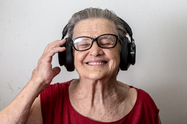 Styl życia i ludzie pojęcie: śmieszna starej damy słuchająca muzyka i taniec na białym tle. starsza kobieta jest ubranym szkła tanczy muzyczny słuchanie na jego hełmofonach. Premium Zdjęcia