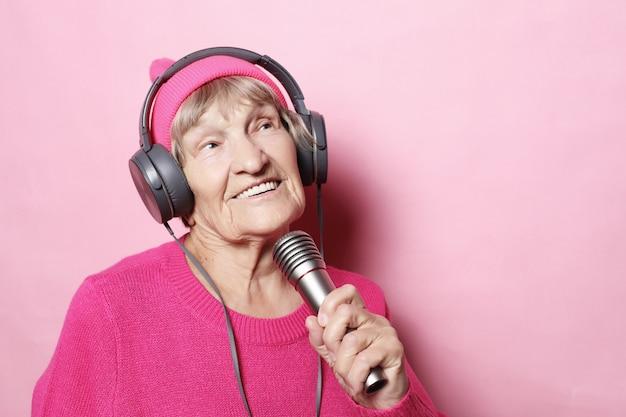 Styl życia i ludzie: zabawna starsza pani słucha muzyki przez słuchawki i śpiewa z mikrofonem Premium Zdjęcia