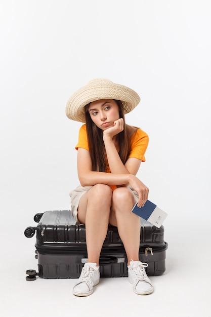 Styl życia i podróże pojęcie: młoda piękna caucasian kobieta siedzi na walizce i czeka na jej lot. odizolowywający nad bielem Premium Zdjęcia