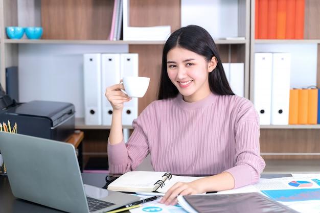Styl życia piękny azjatycki biznes młoda kobieta na biurku biurowym filiżankę gorącej kawy pod ręką Darmowe Zdjęcia