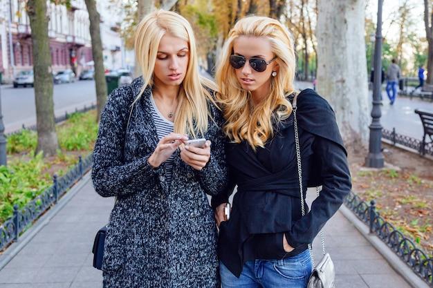 Styl życia Portret Dwóch Najlepszych Przyjaciółek Blondynek Spędzających Czas W Centrum Miasta W ładny Jesienny Jesienny Dzień, Przy Użyciu Smartfona, W Okularach Przeciwsłonecznych I Modnym Wyglądzie. Darmowe Zdjęcia