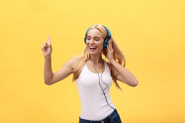 Styl życia portret szczęśliwej kobiety słuchająca muzyka w hełmofonach odizolowywających na żółtym tle Premium Zdjęcia