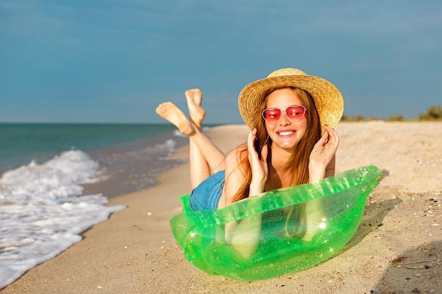 Styl życia Portret Szczęśliwej Piękności Blondynki Leżącej W Materacu, Opalając Się Na Plaży, Uśmiechając Się I Ciesząc Się Wakacjami Darmowe Zdjęcia