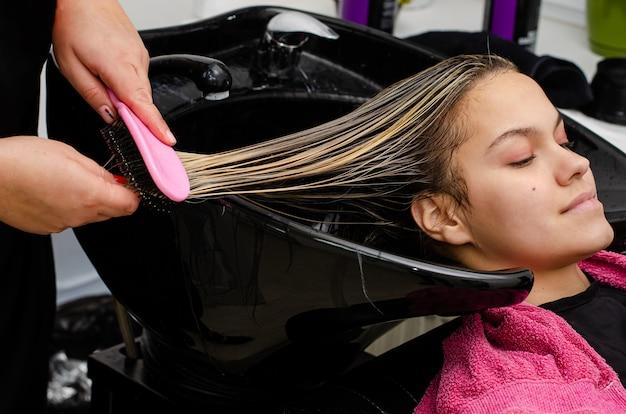 Stylista Włosów Nakładający Maskę Na Włosy I Czesający Mokre Włosy Klientów Szczoteczką W Czarnym Zlewie Premium Zdjęcia