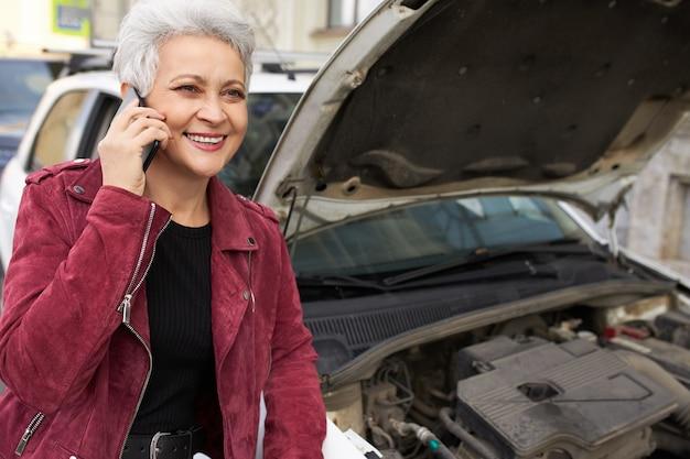 Stylowa Atrakcyjna Siwowłosa Dojrzała Kobieta Kierowca Stojąca Obok Zepsutego Białego Samochodu Z Otwartą Maską I Rozmawiająca Przez Telefon Darmowe Zdjęcia