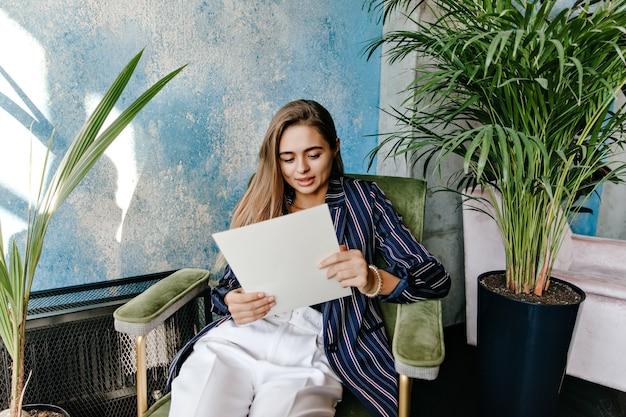 Stylowa Biznesowa Kobieta Pozuje W Biurze Z Gazetą. Atrakcyjna Dziewczynka Kaukaski Czytanie Dokumentów. Darmowe Zdjęcia
