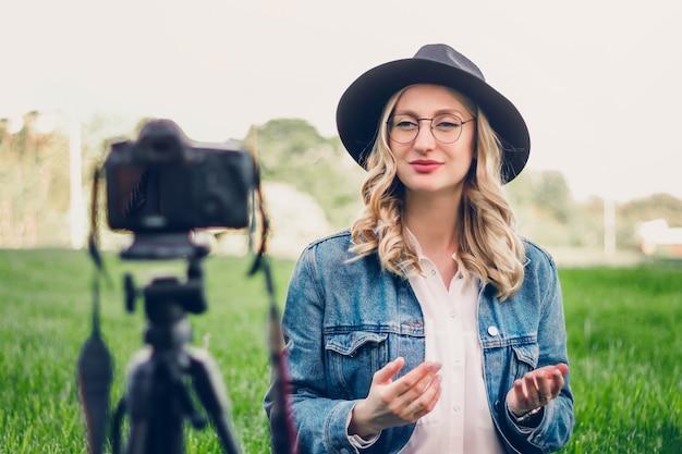 Stylowa blogerka siedząca w parku i fotografująca vlog na aparacie. Premium Zdjęcia