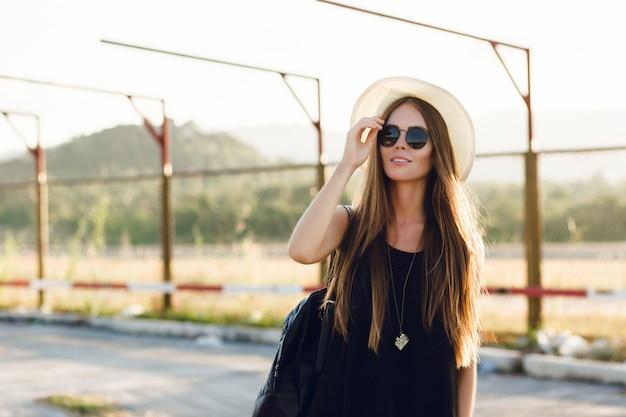 Stylowa Dziewczyna Stojąca W Pobliżu Drogi Na Sobie Krótką Czarną Sukienkę, Słomkowy Kapelusz, Czarne Okulary I Czarny Plecak. Uśmiecha Się W Ciepłych Promieniach Zachodzącego Słońca. Dotyka Ręką Okularów Przeciwsłonecznych Darmowe Zdjęcia