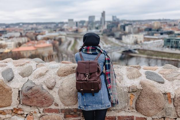 Stylowa Dziewczyna W Dżinsowej Kurtce Chodzi Przy Vilnius Tłem Premium Zdjęcia