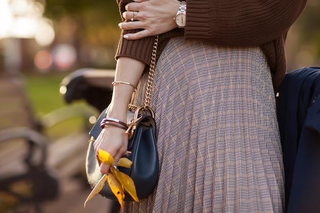 Stylowa dziewczyna w jesiennym parku w brązowym swetrze i spódnicy w kratę. Premium Zdjęcia