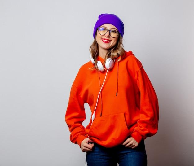 Stylowa dziewczyna w pomarańczowej bluzie i fioletowym kapeluszu ze słuchawkami Premium Zdjęcia