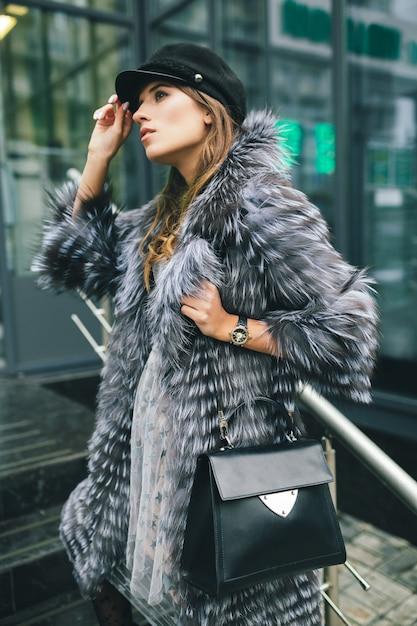Stylowa Kobieta Spacerująca Po Mieście W Ciepłym Futrze, Sezon Zimowy, Zimna Pogoda, Ubrana W Czarną Czapkę, Trzymająca Skórzaną Torbę, Trend W Modzie Ulicznej, Miejski Look Darmowe Zdjęcia