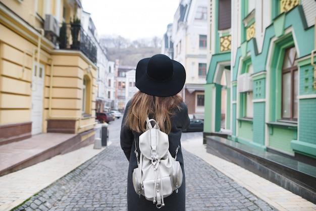 Stylowa Kobieta Spacerująca Ulicami Pięknego Starego Miasta. Premium Zdjęcia