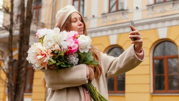 Stylowa Kobieta Trzyma Bukiet Kwiatów Na Zewnątrz Wiosną I Przy Selfie Darmowe Zdjęcia
