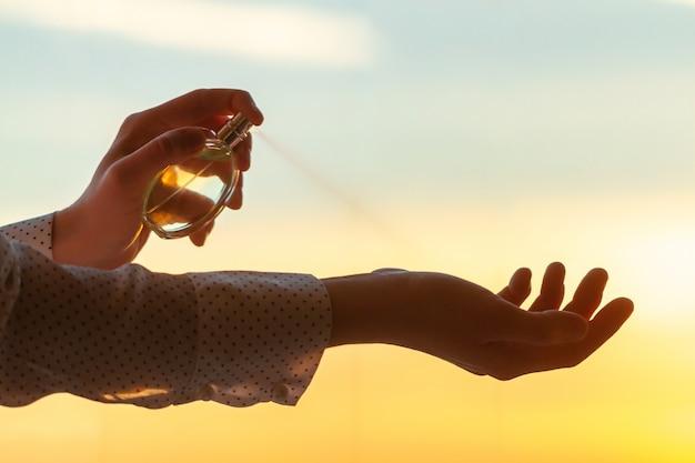 Stylowa Kobieta W Bluzce Stosowania Perfum Na Jej Nadgarstku O Zachodzie Słońca Premium Zdjęcia