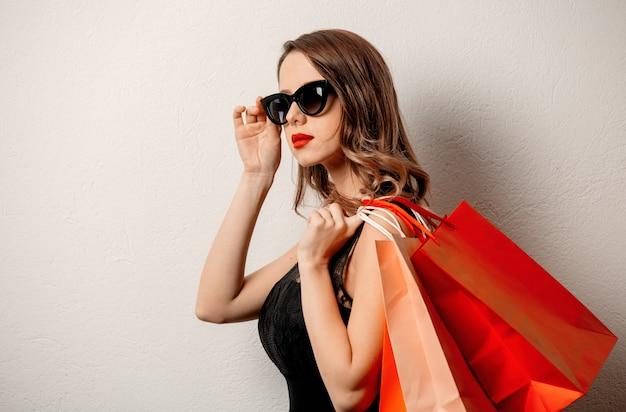 Stylowa Kobieta W Okularach Przeciwsłonecznych Z Torba Na Zakupy Na Biel ścianie Premium Zdjęcia