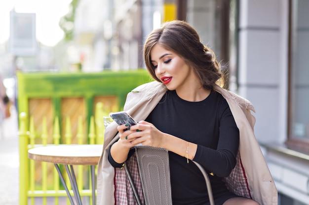 Stylowa Kobieta Z Czerwonymi Ustami Ubrana W Beżowy Płaszcz Przewijający Smartfon Siedząc W Kawiarni Na świeżym Powietrzu Darmowe Zdjęcia
