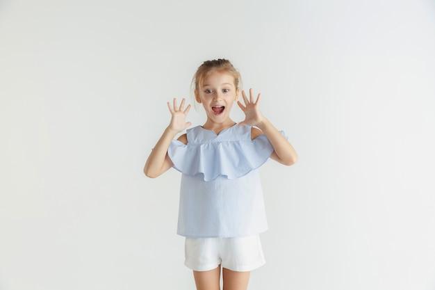 Stylowa Mała Uśmiechnięta Dziewczyna Pozuje W Ubranie Na Białym Tle Na Tle Białego Studia. Kaukaski Blond Modelka. Ludzkie Emocje, Wyraz Twarzy, Dzieciństwo, Sprzedaż. Zszokowany, Zdumiony. Darmowe Zdjęcia