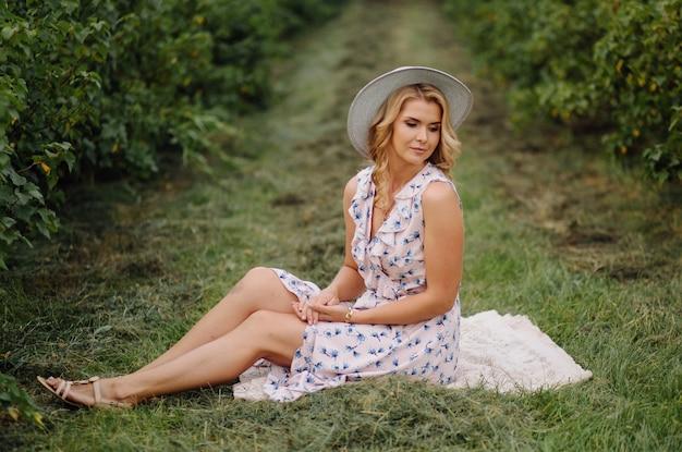 Stylowa Młoda Kobieta W Różowej Niebieskiej Sukience Vintage I Kapeluszu Pozowanie W Zielonym Polu Darmowe Zdjęcia