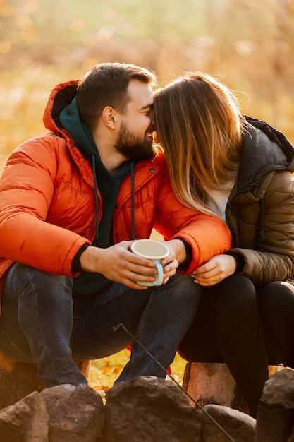 Stylowa para z filiżanką kawy w pobliżu ogniska Premium Zdjęcia