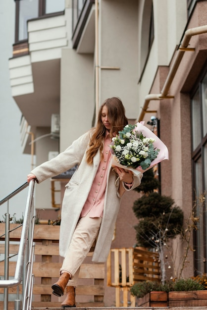 Stylowa Szczęśliwa Kobieta Trzyma Bukiet Kwiatów Na Zewnątrz W Mieście Premium Zdjęcia