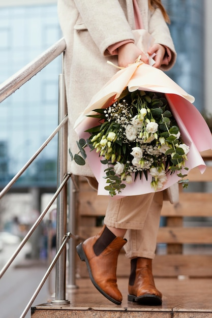 Stylowa Szczęśliwa Kobieta Trzyma Bukiet Kwiatów Na Zewnątrz Premium Zdjęcia