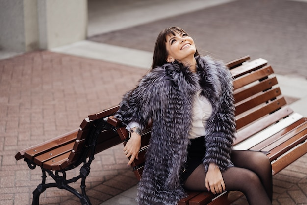 Stylowa Uśmiechnięta Brunetka Z Długimi Prostymi Włosami Ubrana W Futro Umiejscowione Na ławce I Patrząca W Niebo Premium Zdjęcia