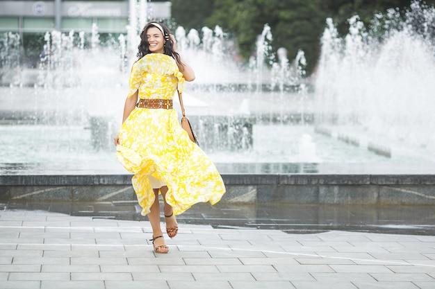 Stylowe Młoda Kobieta Spaceru. Miejska Dziewczyna. Modna Kobieta. Pełny Wzrost Strzelał Piękna Kobieta W żółtej Sukni. Premium Zdjęcia