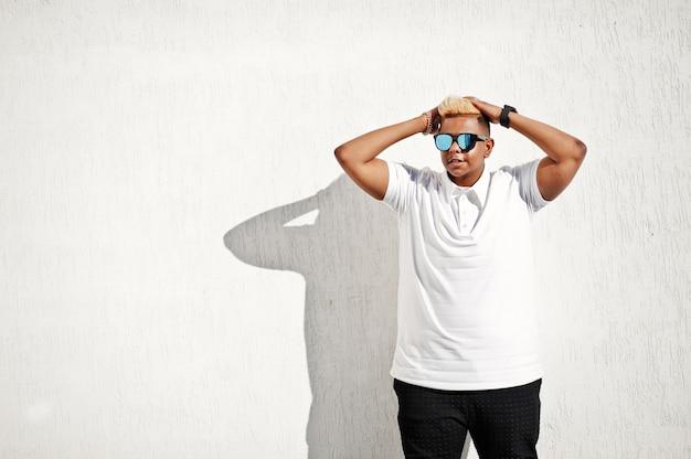 Stylowy Arabski Muzułmanin Z Oryginalnymi Włosami I Okularami Przeciwsłonecznymi Postawionymi Na Ulicach Przy Dachu Przy Białej ścianie. Premium Zdjęcia