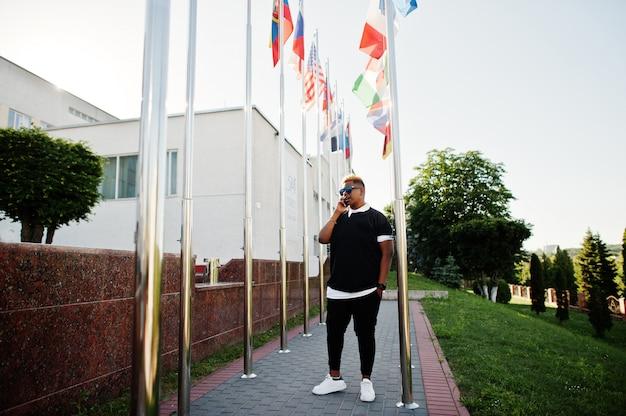 Stylowy Arabski Muzułmanin Z Oryginalnymi Włosami Postawionymi Na Ulicach, Na Flagach Różnych Krajów. Premium Zdjęcia